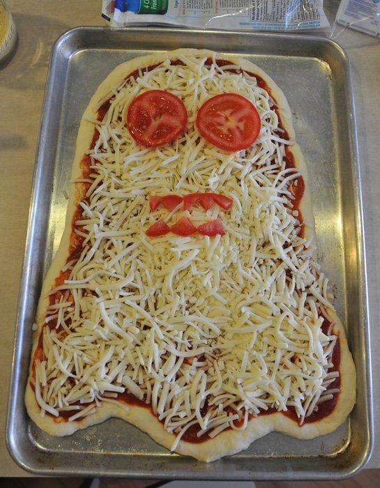 Ghost Pizza on a baking sheet before baking