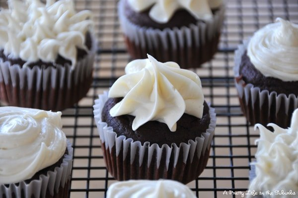 chocolate beet cupcakes topped with piped white icing. they sit on a black wire cooling rack