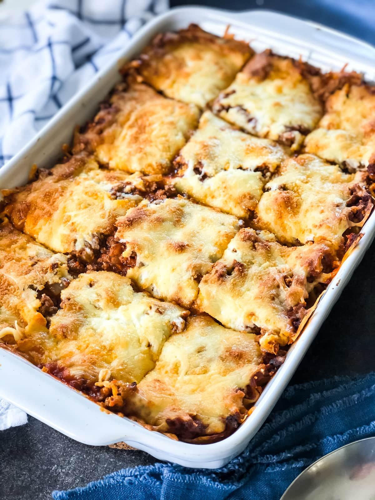 A dish of lasagna cut into 12 pieces