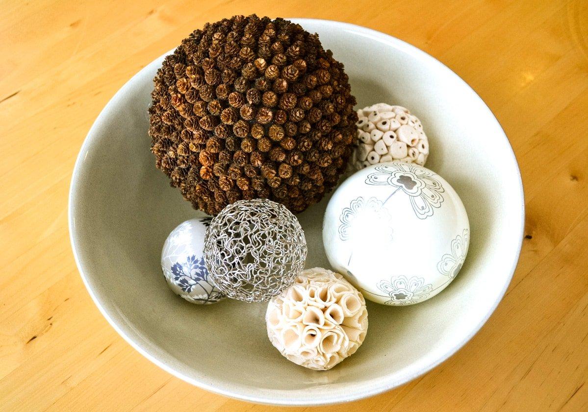 A Teeny Tiny Pine Cone Pomander in a bowl of decorative balls