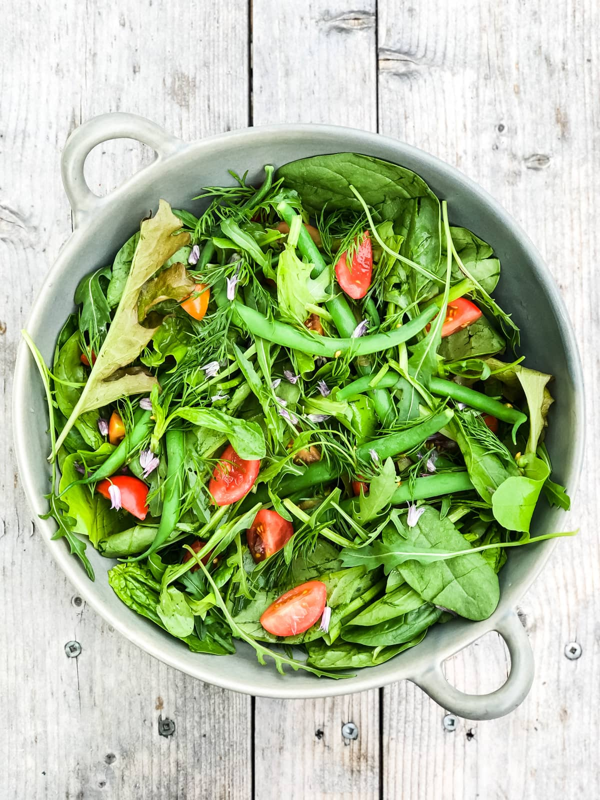a top down view of a Simple Green Salad loaded with fresh greens, green beans, herbs and sliced tomatoes