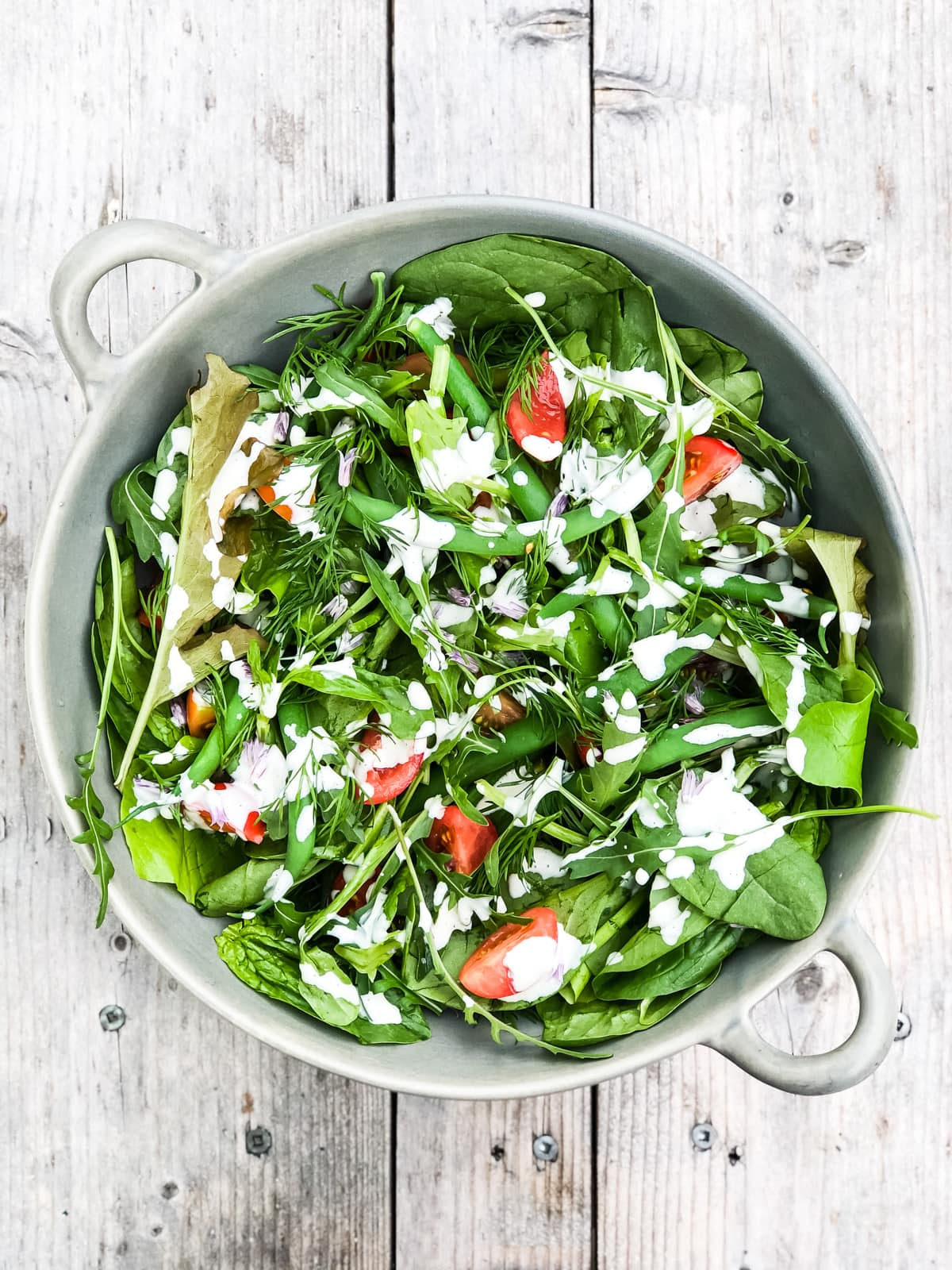 a top down view of a Simple Green Salad loaded with fresh greens, green beans, herbs and sliced tomatoes, then drizzled with a white dressing