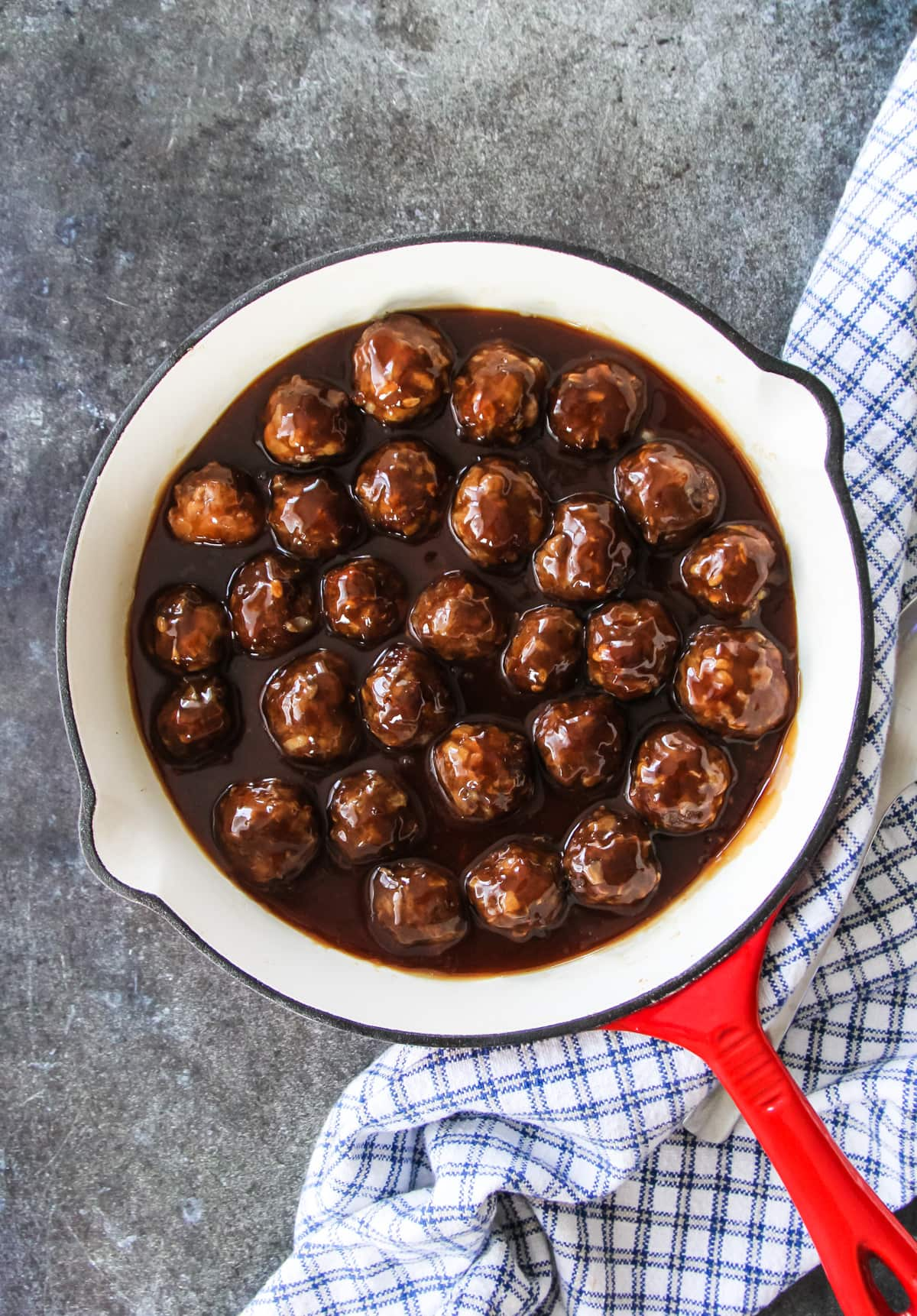 an enamel pan filled with sweet and sour meatballs. sitting on a grey background and blue checked towel
