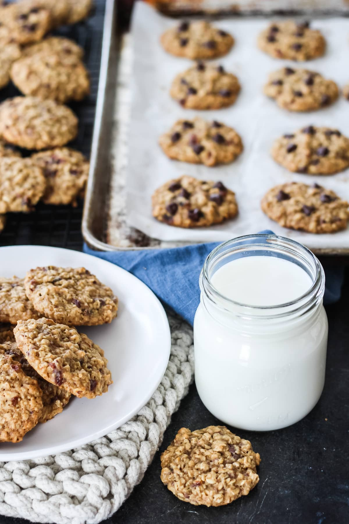 a mason jar glass of milk, a plate of oatmeal raisin cookies. in the background is a cookie sheet of more cookies