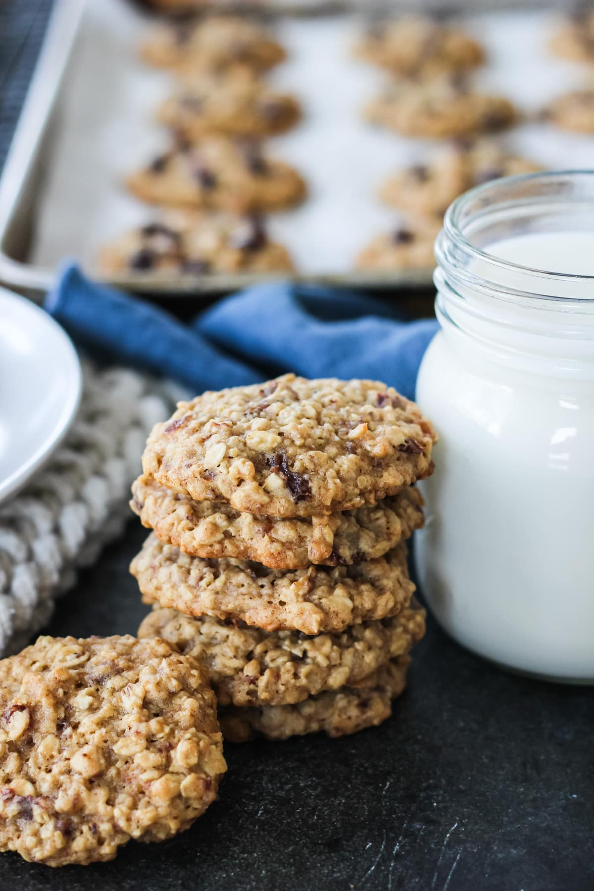 a stack of Oatmeal Raisin Cookies beside a glass of milk