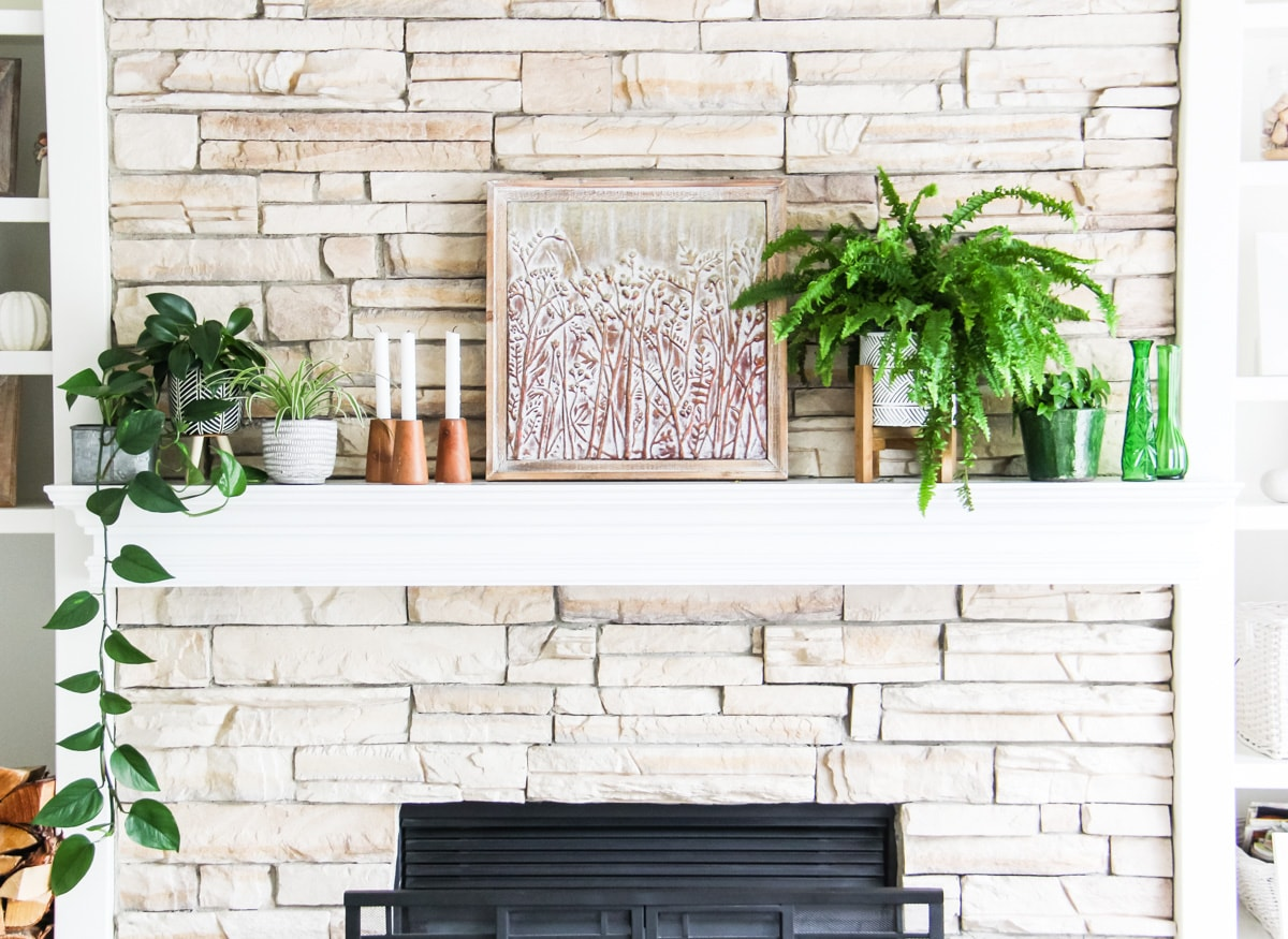 a front view of a light stone fireplace mantel decorated with plants, candles and art.