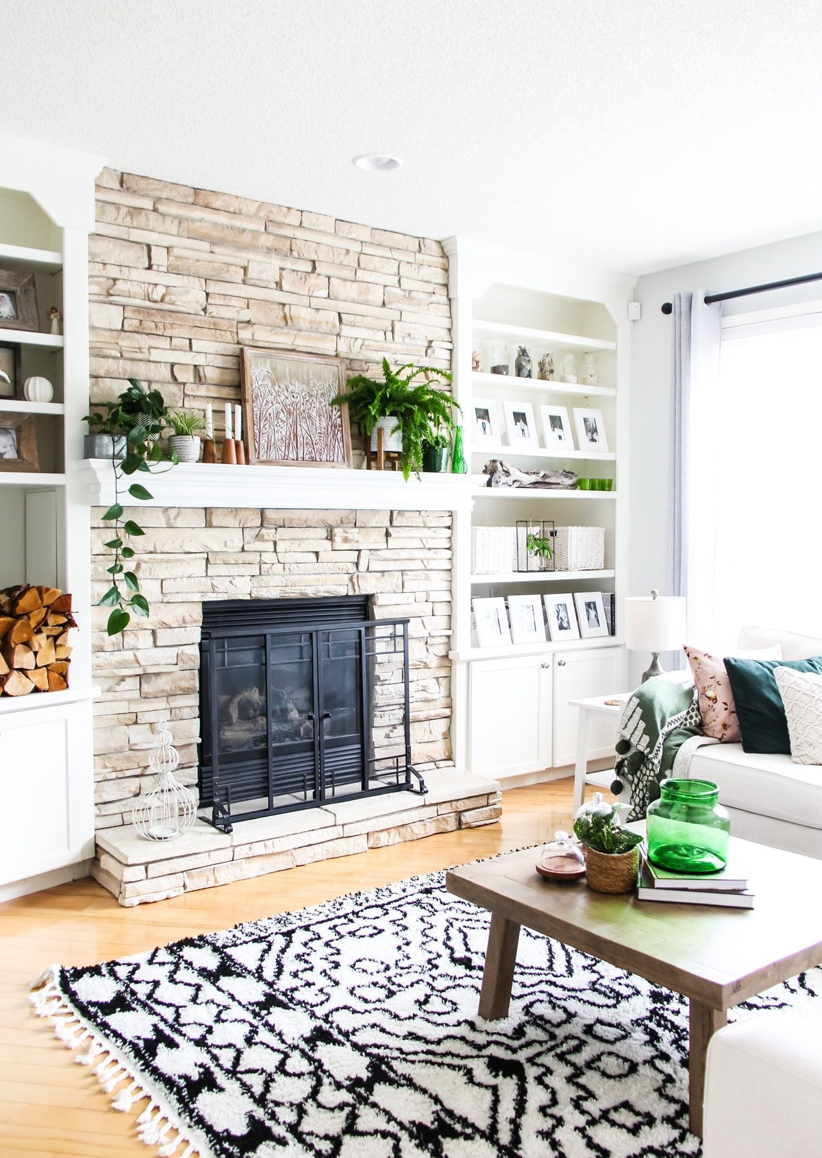 a side view of a light stone fireplace decorated with plants, candles and art. there are shelves filled with white framed pictures, baskets and pops of green. in the foreground is a wooden coffee table on a black and white rug