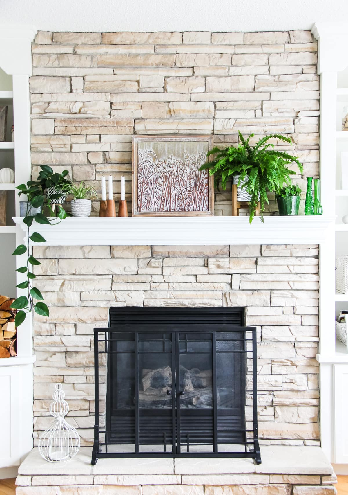 a front view of a light stone fireplace decorated with plants, candles and art.