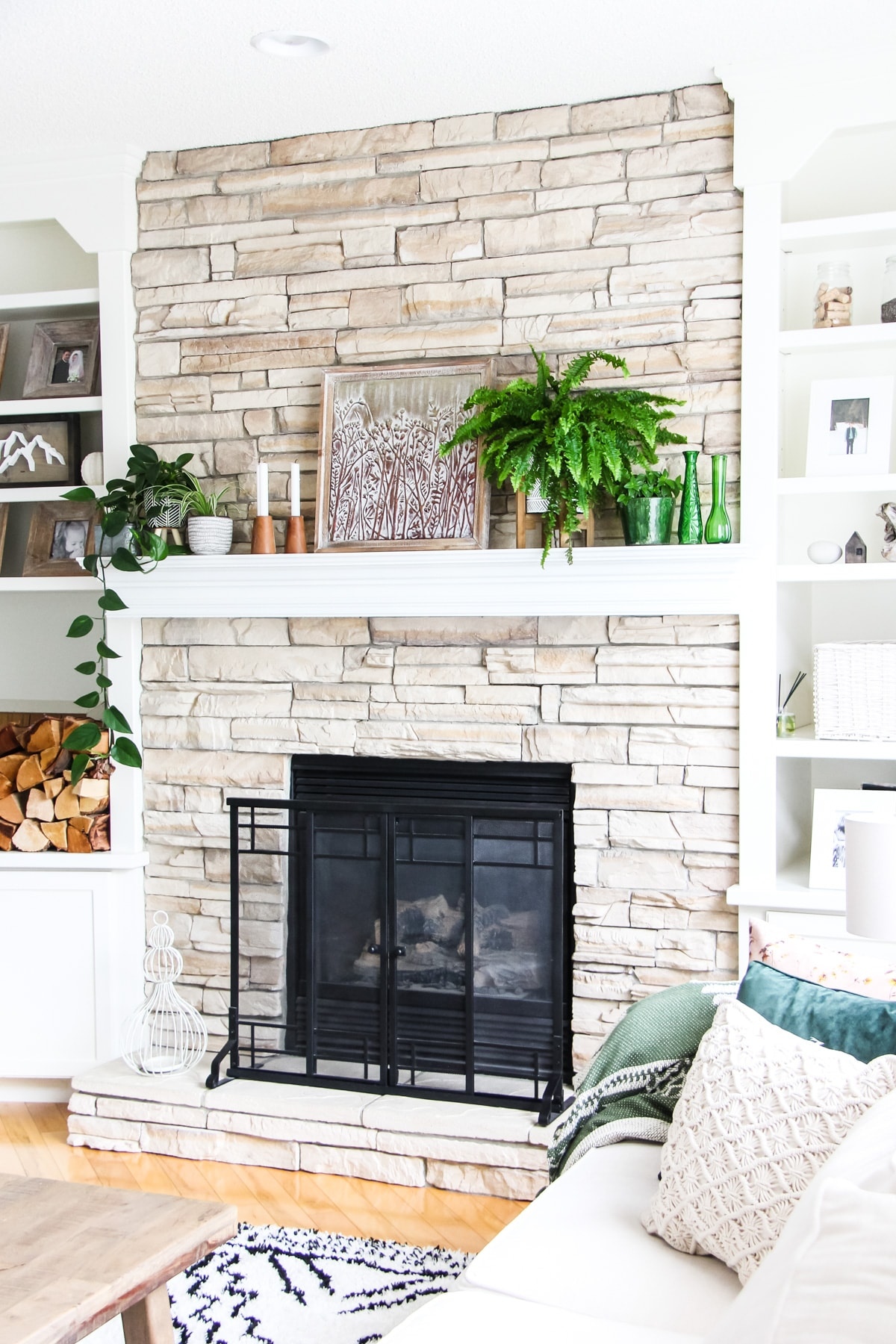 a side view of a light stone fireplace decorated with plants, candles and art.