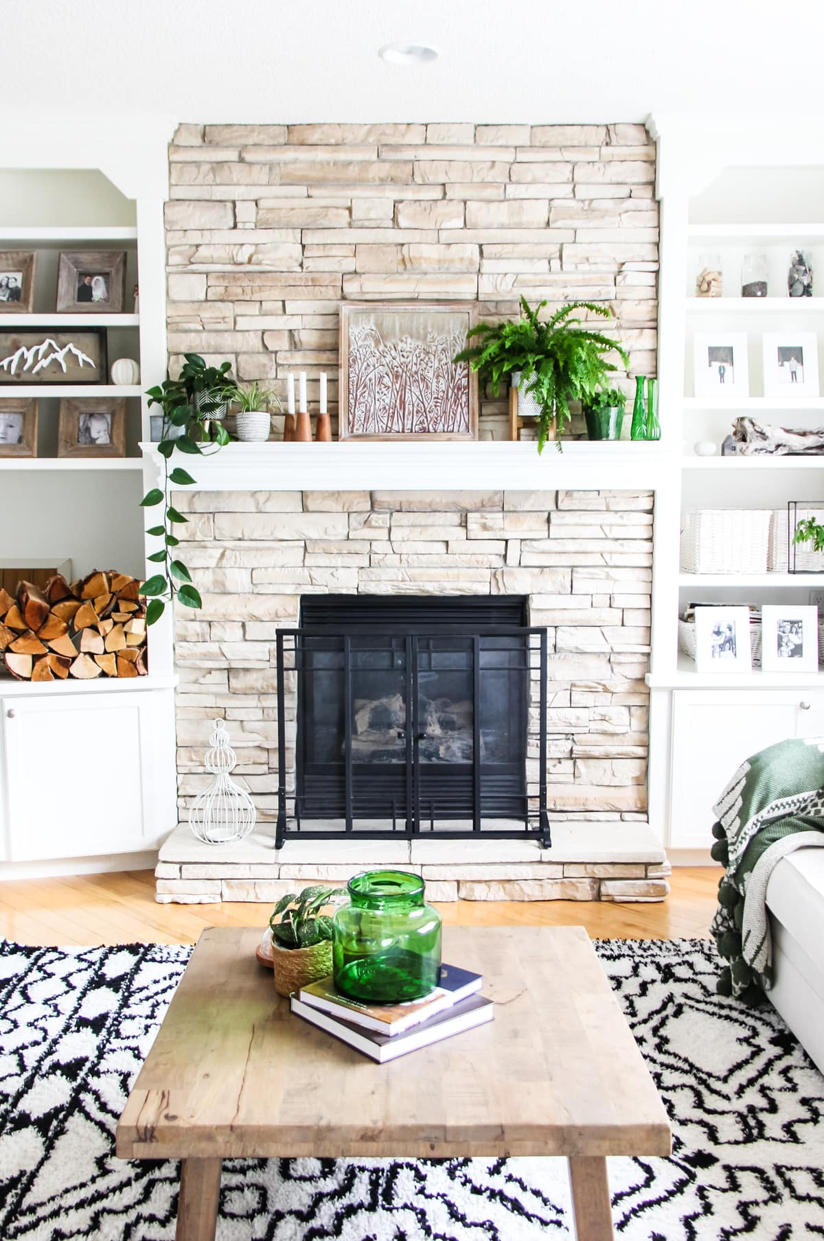 a front view of a light stone fireplace decorated with plants, candles and art. on either side are white built in shelves filled with white framed pictures, baskets and pops of green. in the forefront is a wooden coffee table with a green vase and plant