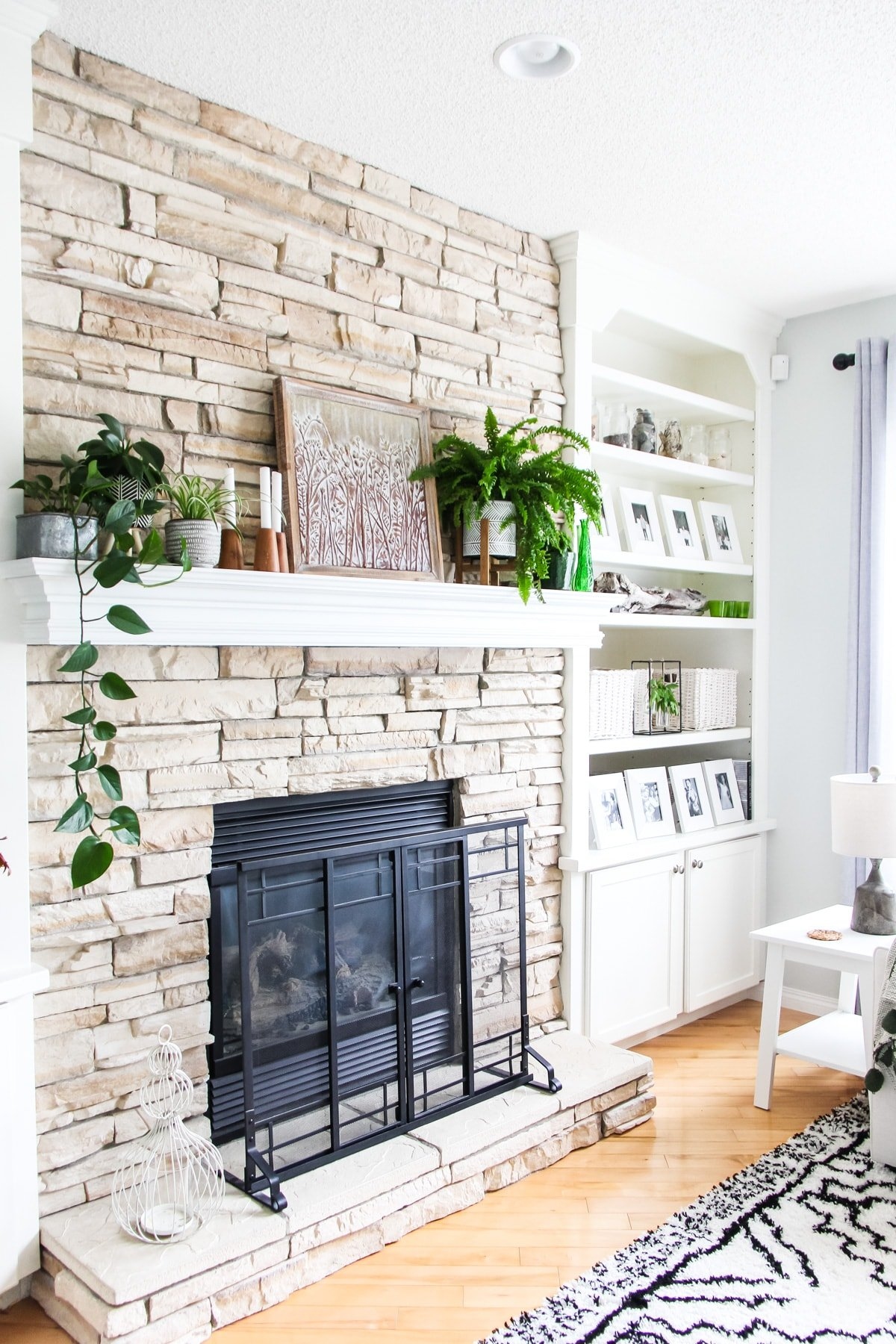a side view of a light stone fireplace decorated with plants, candles and art. there are shelves filled with white framed pictures, baskets and pops of green.