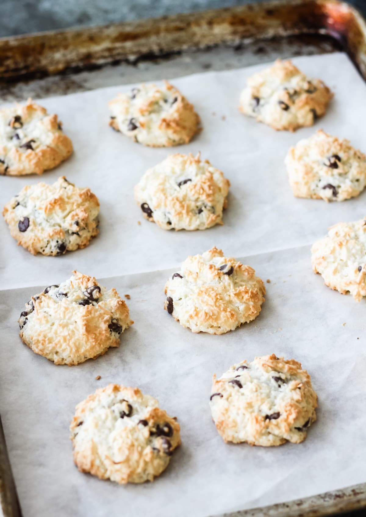 a parchment paper lined cookie sheet of freshly baked Chocolate Chip Coconut Macaroons