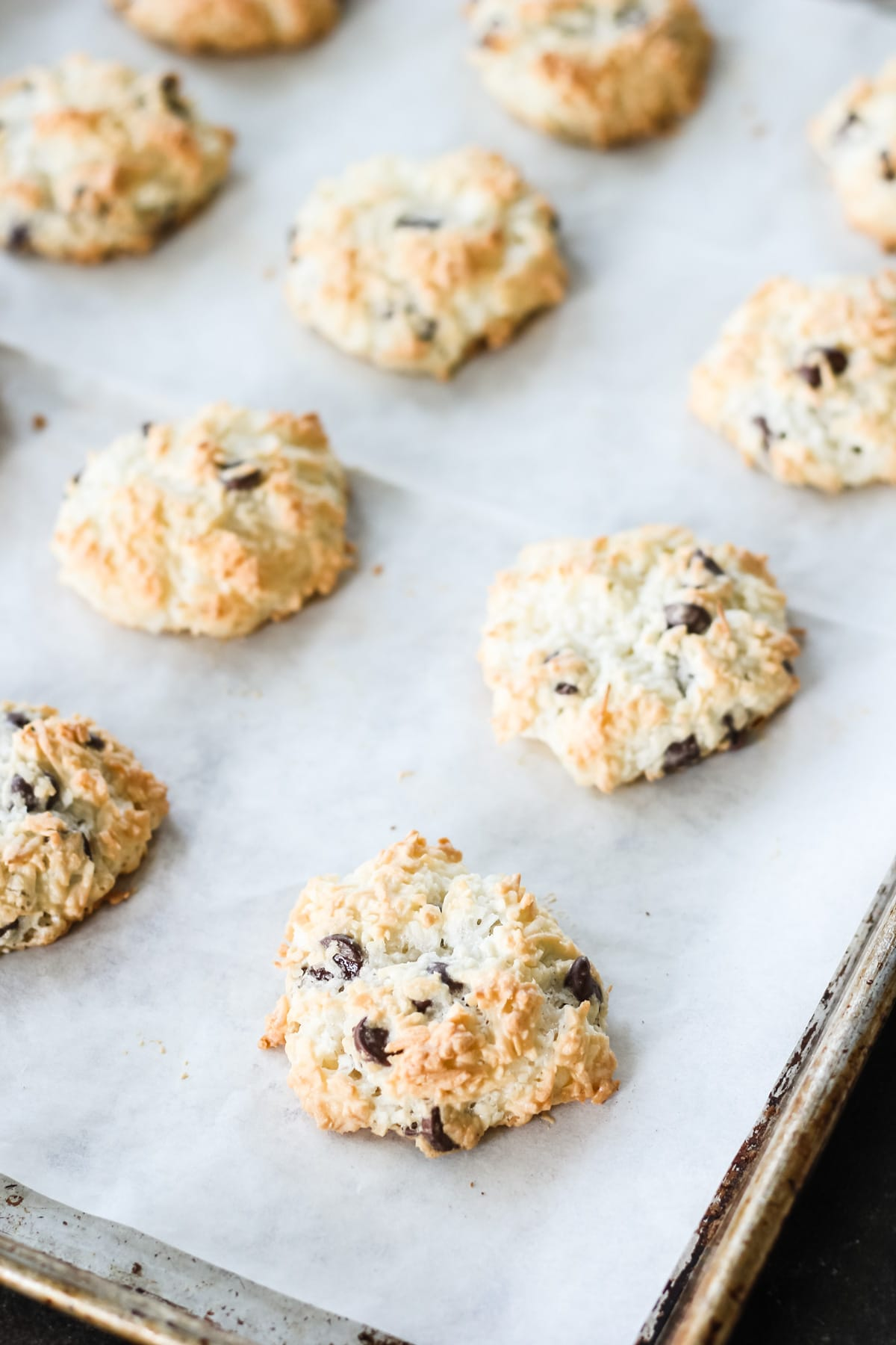 a close up view of freshly baked Chocolate Chip Coconut Macaroons on a parchment paper lined cookie sheet