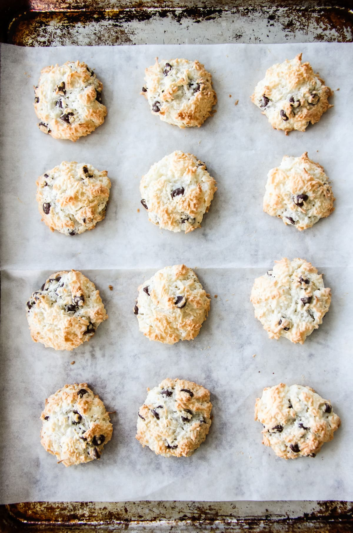 a top down view of freshly baked Chocolate Chip Coconut Macaroons on a parchment paper lined cookie sheet