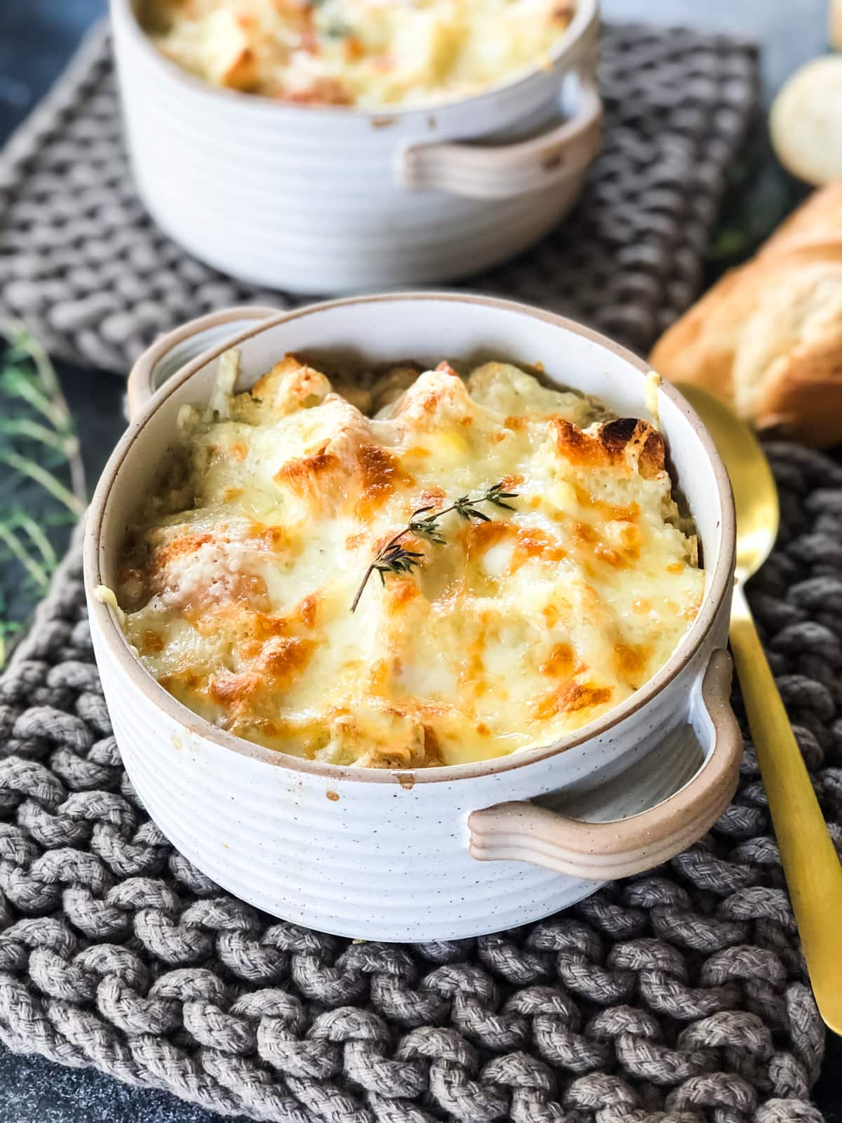 A view of a bowl of French Onion Soup topped with a cheesy bread crust.