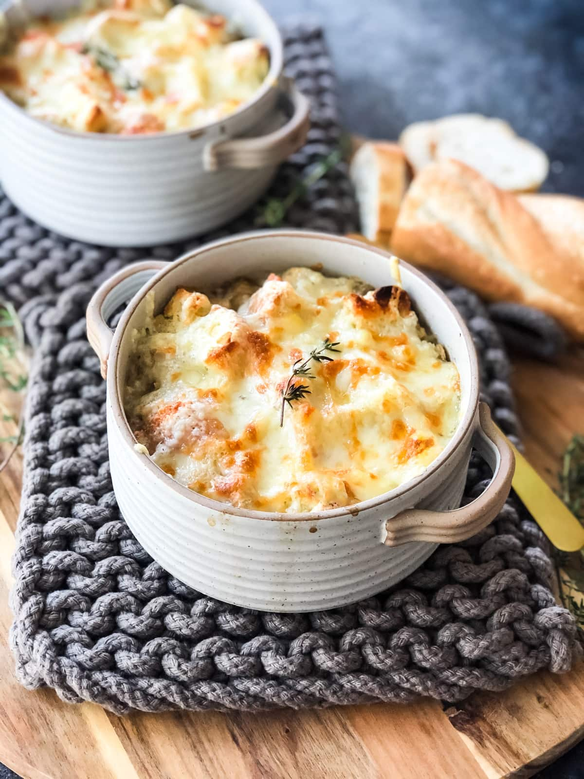 Two bowls of French Onion Soup topped with a cheesy bread crust.