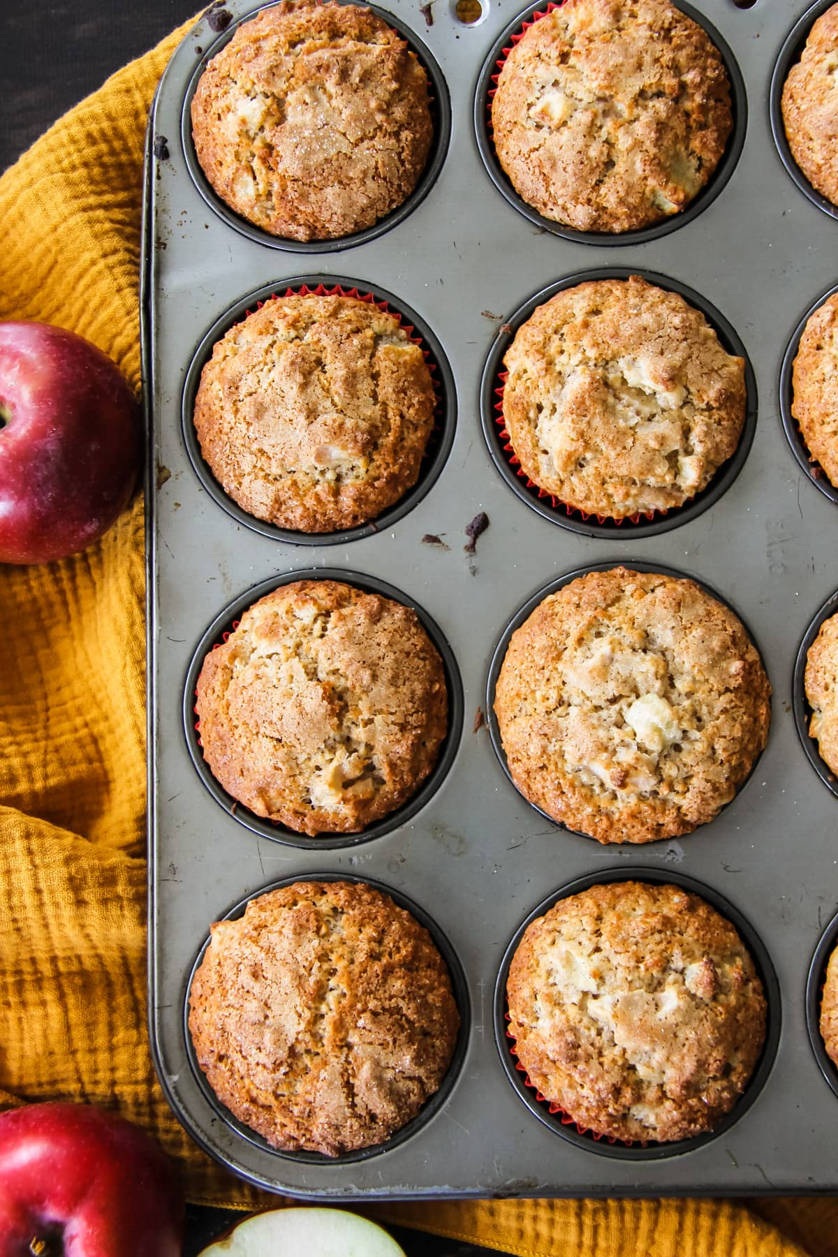 a top down view of a muffin tin filled with fresh baked muffins. in the background is a mustard yellow napkin and red apples