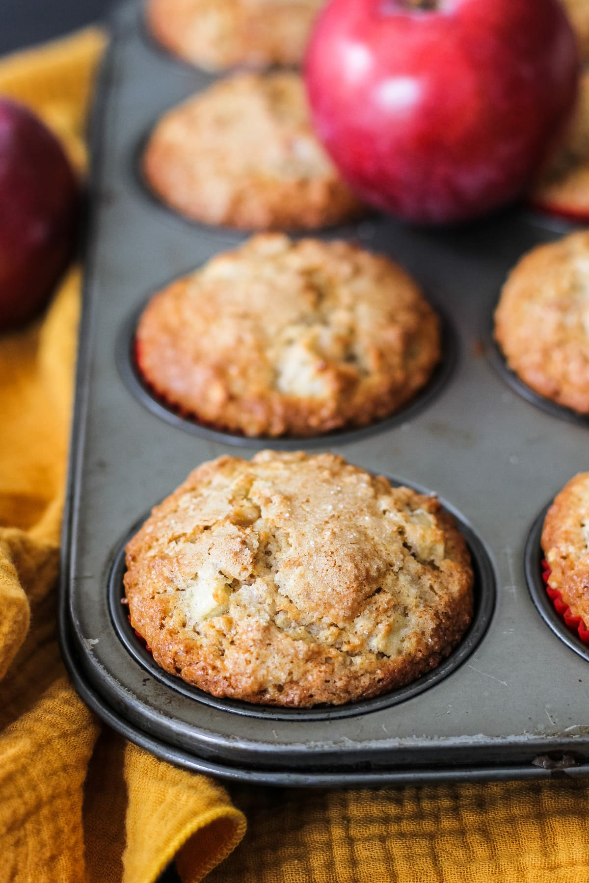 a close up of a maple apple muffin in a muffin tin. in the background is a red apple