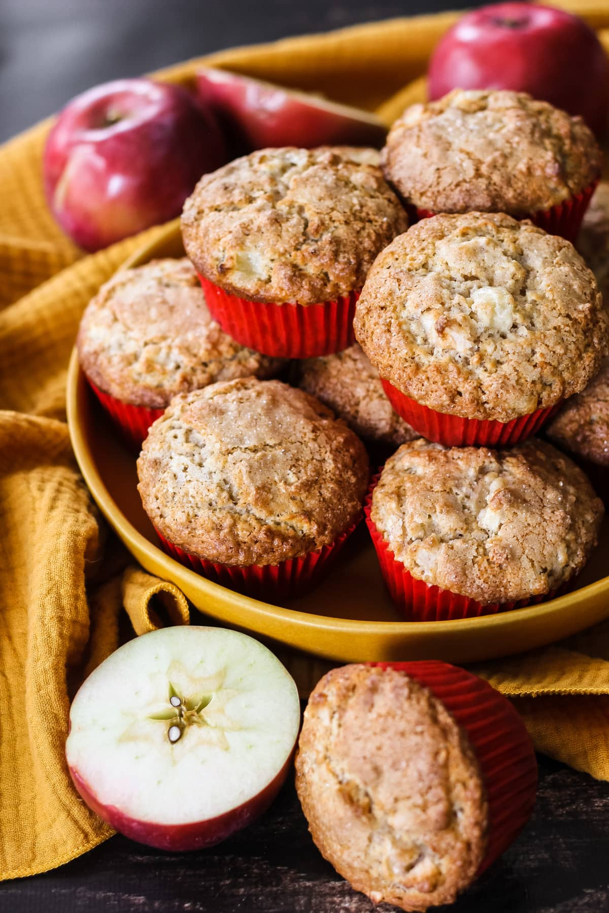 a mustard yellow bowl filled with stacked baked maple apple muffins. in the background are red apples and a mustard yellow napkin