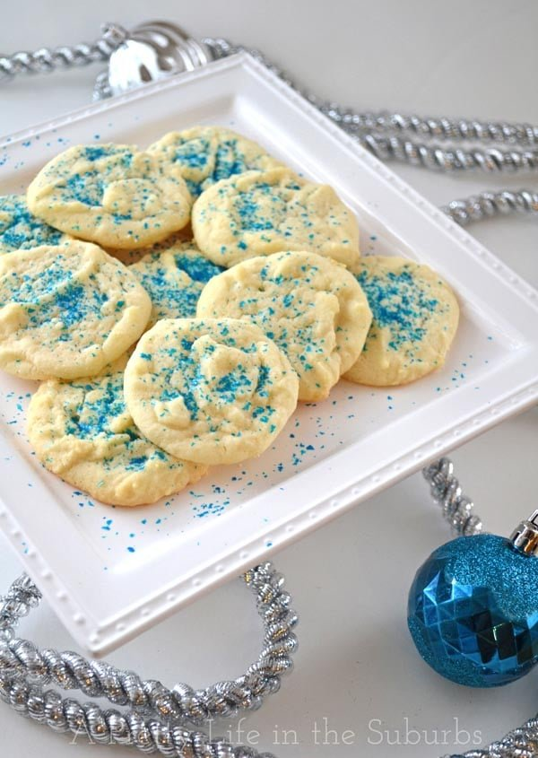 a plate of sugar cookies decorated with edible blue sprinkles