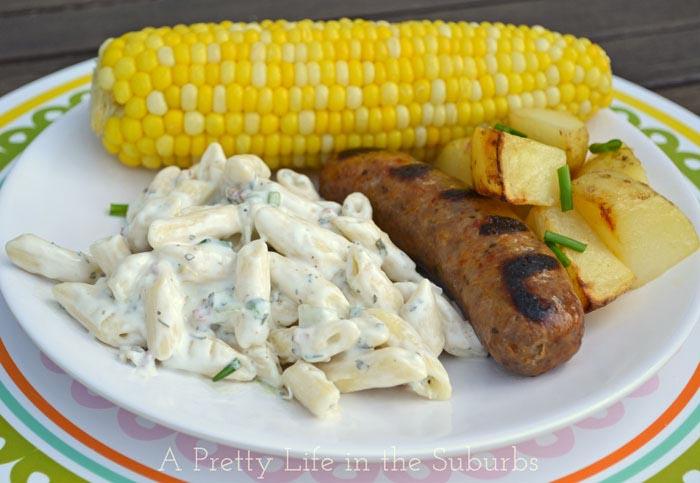 A plate of macaroni salad, sausage and corn on the cob