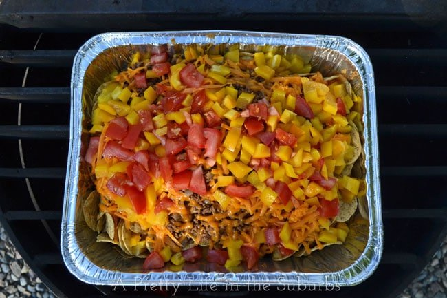 Delicious Camping Recipes: a top down view of a pan of nachos cooking over a fire grill