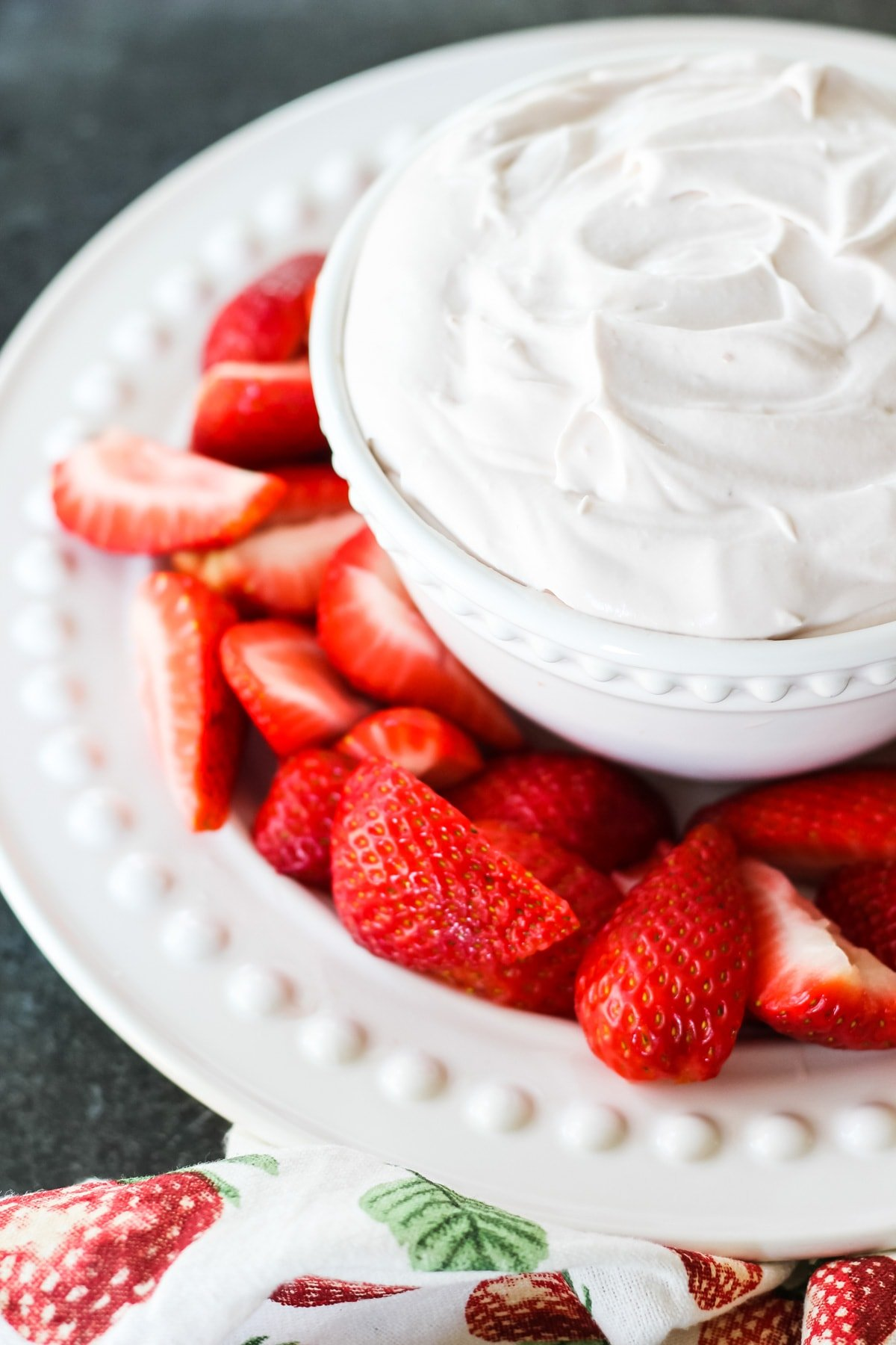 a white bowl filled with Strawberry Fluff Fruit Dip. the bowl is nestled on a plate with sliced strawberries