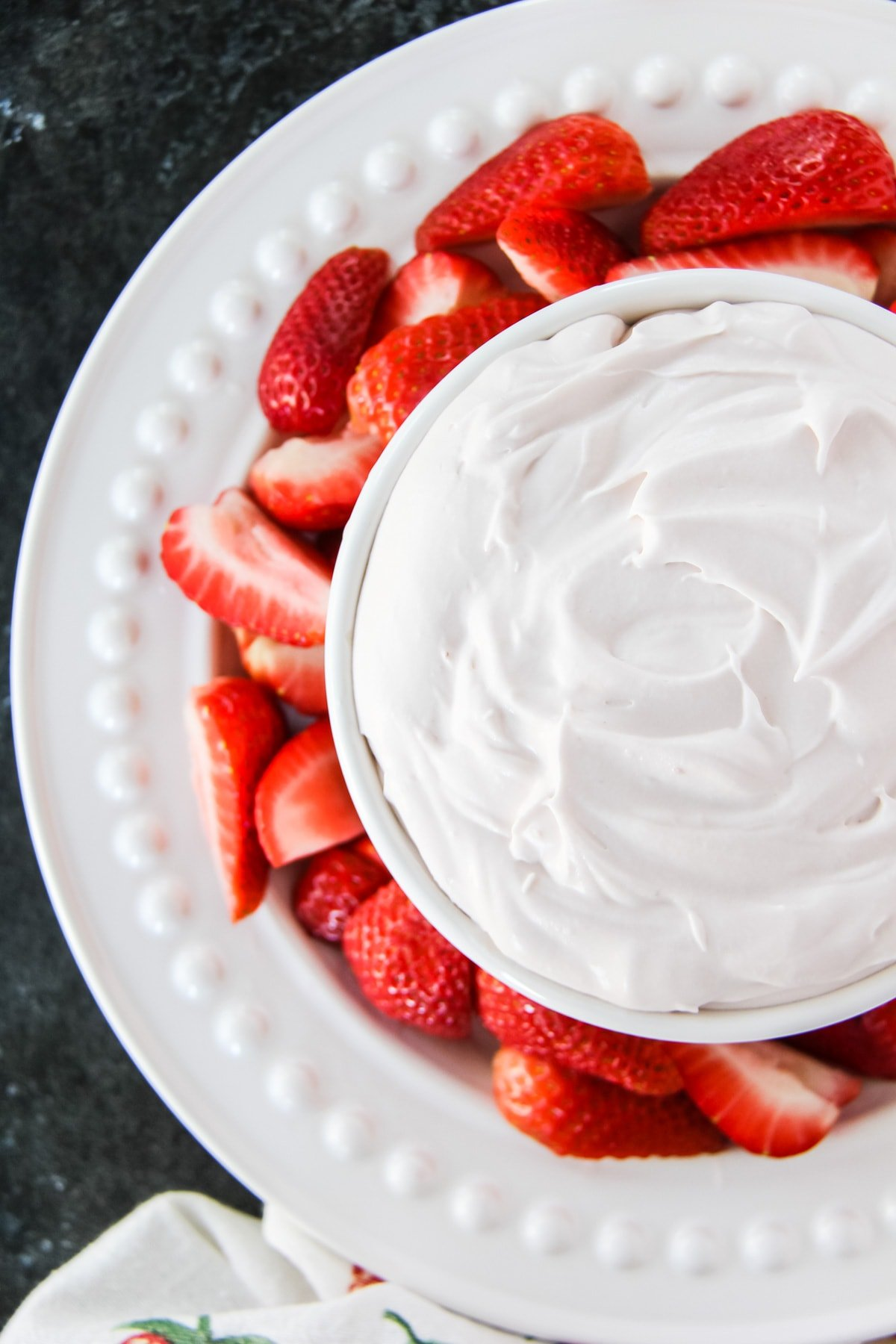 a top down view of a white bowl filled with Strawberry Fluff Fruit Dip. the bowl is nestled on a plate with sliced strawberries.