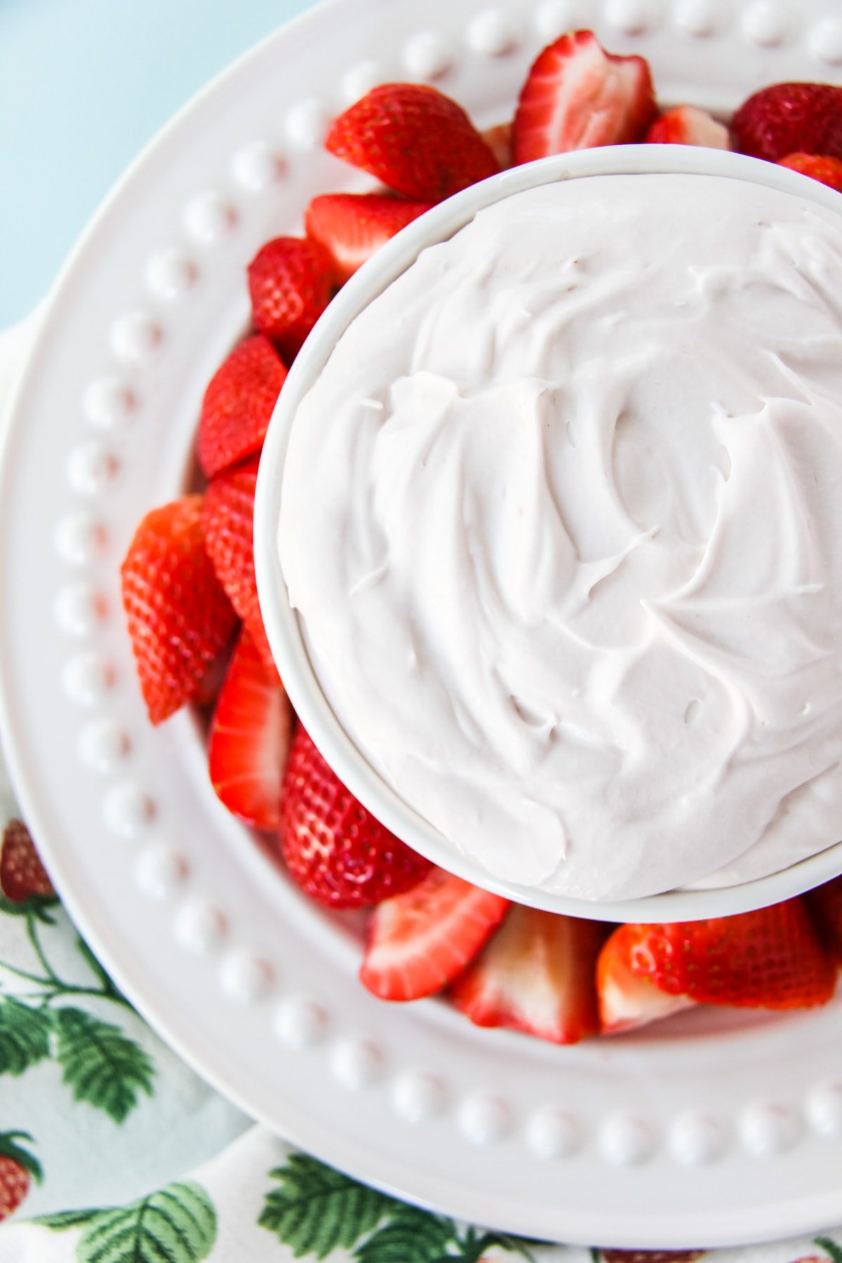 a top down view of a white bowl filled with Strawberry Fluff Fruit Dip. the bowl is nestled on a plate with sliced strawberries. in the background is a strawberry print tea towel
