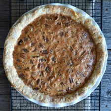 A top down view of a pecan pie on a cooling rack