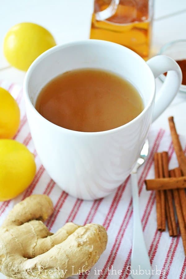 A mug of Ginger Tea, and cinnamon sticks, ginger root and lemons