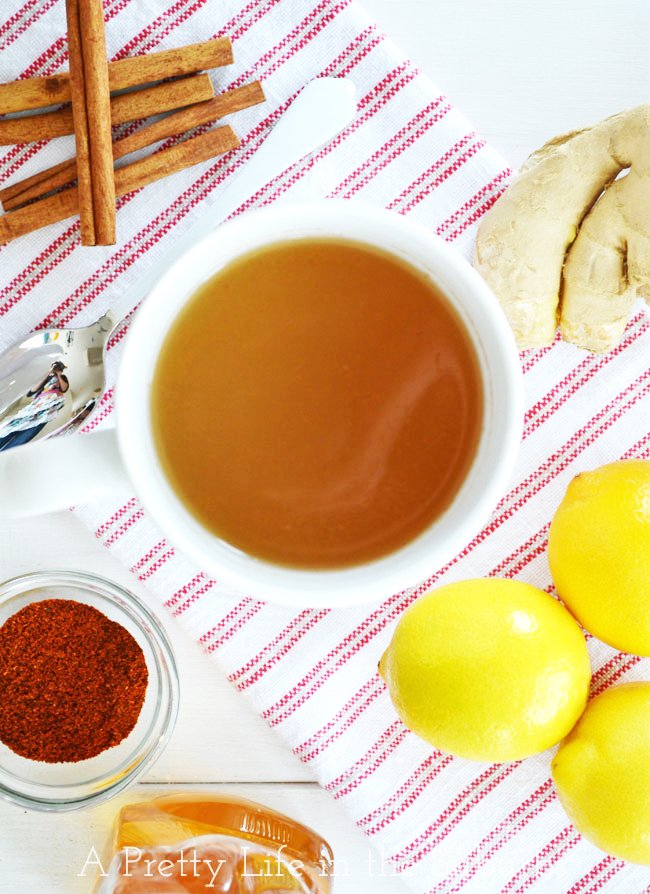 A top down view of a mug of Ginger Tea, and cinnamon sticks, ginger root and lemons