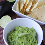 A bowl of Jalapeno & Lime Guacamole next to a bowl of tortilla chips