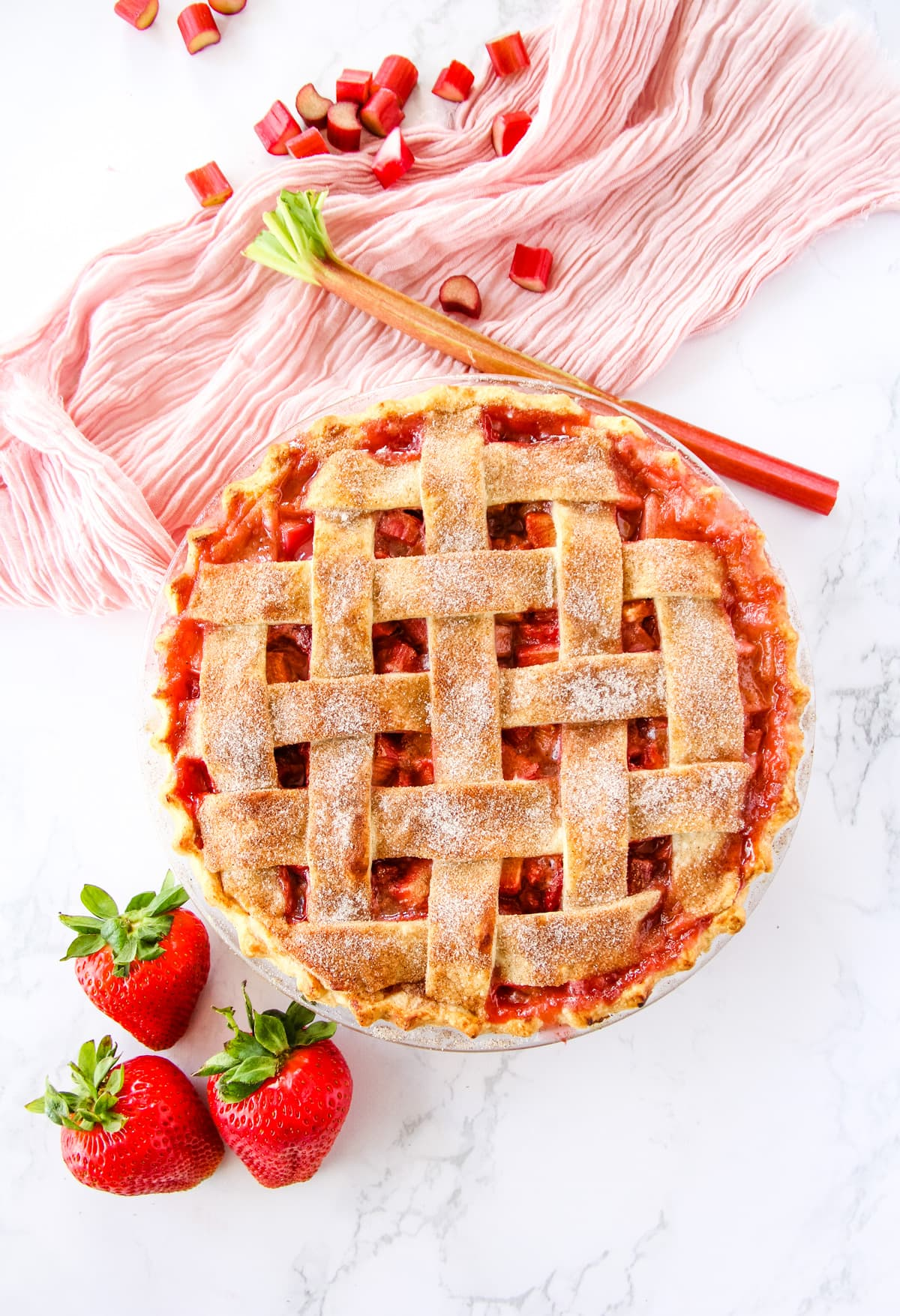a top down view of a strawberry rhubarb pie with a lattice crust. in the background is a soft pink napkin, chopped rhubarb and three strawberries