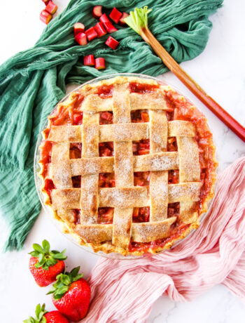 a top down view of a strawberry rhubarb pie with a lattice crust. in the background are a green napkin and a soft pink napkin, chopped rhubarb, three strawberries and a pie cutter