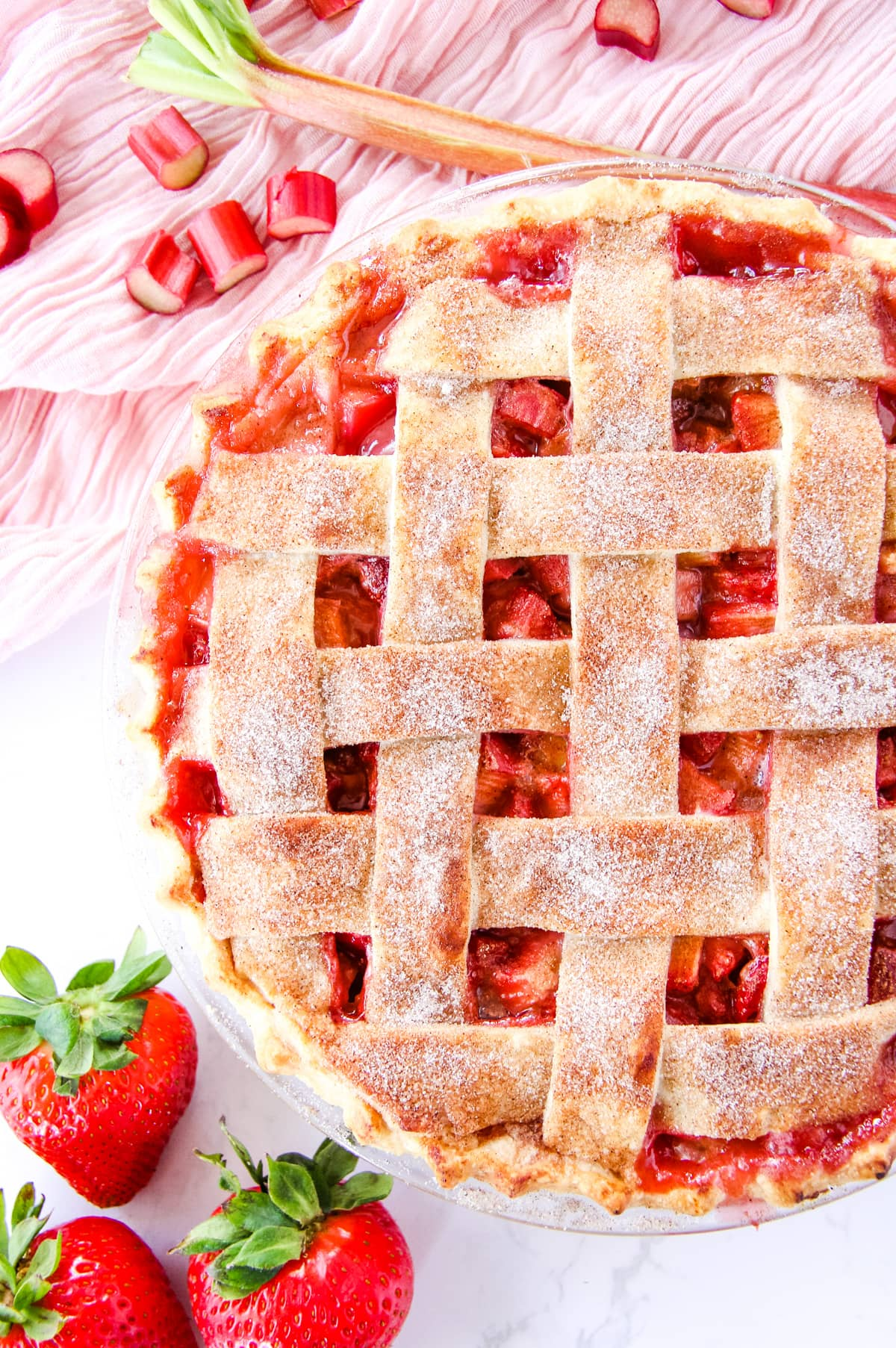a top down view of half of a strawberry rhubarb pie with a lattice crust. in the background is a soft pink napkin, chopped rhubarb and strawberries