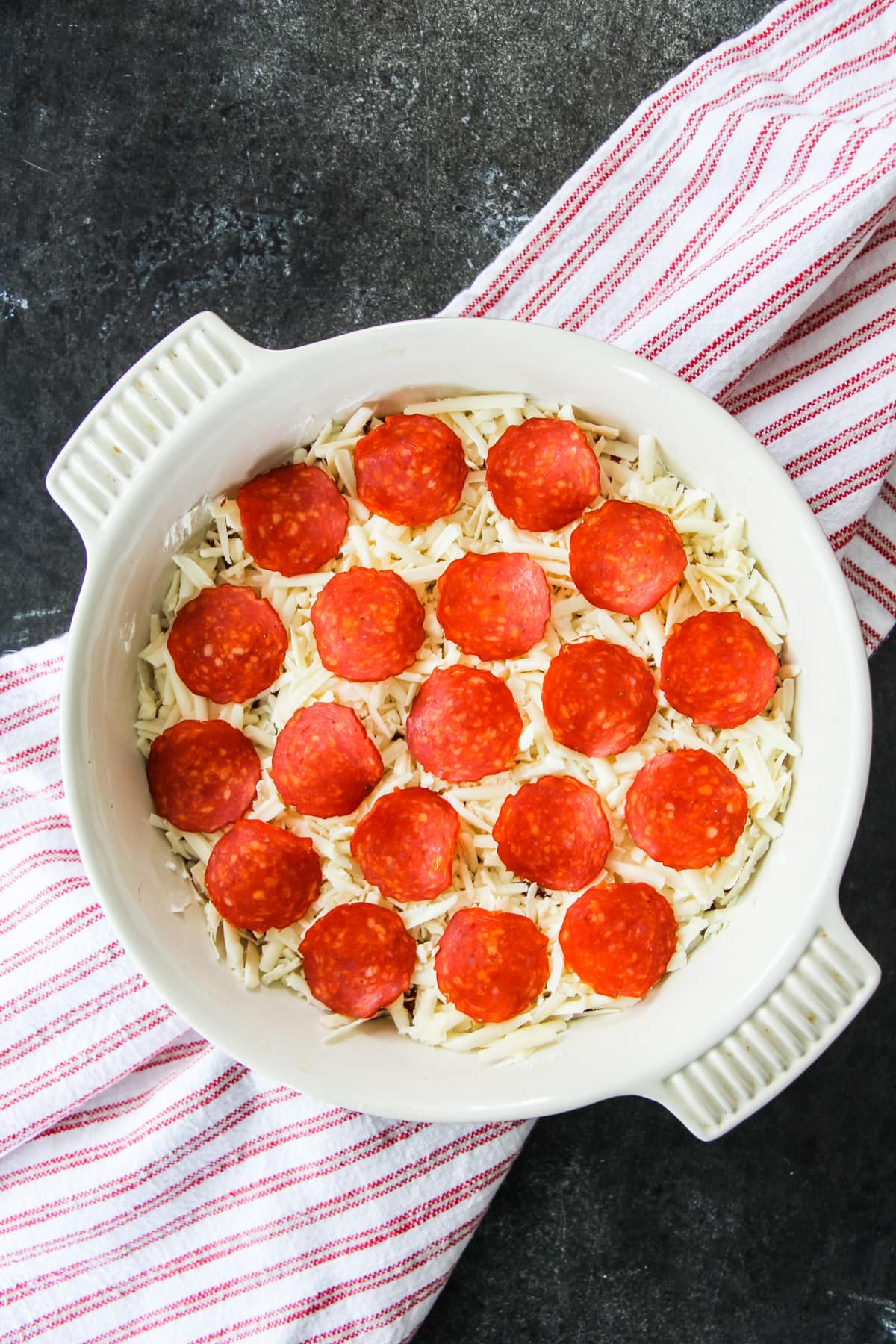 a top down view of an unbaked pizza dip with pepperoni. in the background is a red and white striped towel