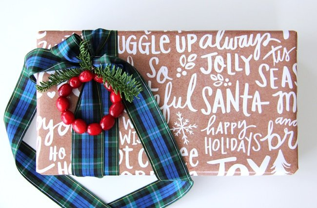 a Christmas gift wrapped in brown paper with white lettering. decorated with a blue and green plaid ribbon, sprigs of fir and a mini fresh cranberry wreath