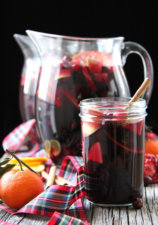 two jugs and a mason jar full of red wine sangria. set against a black background
