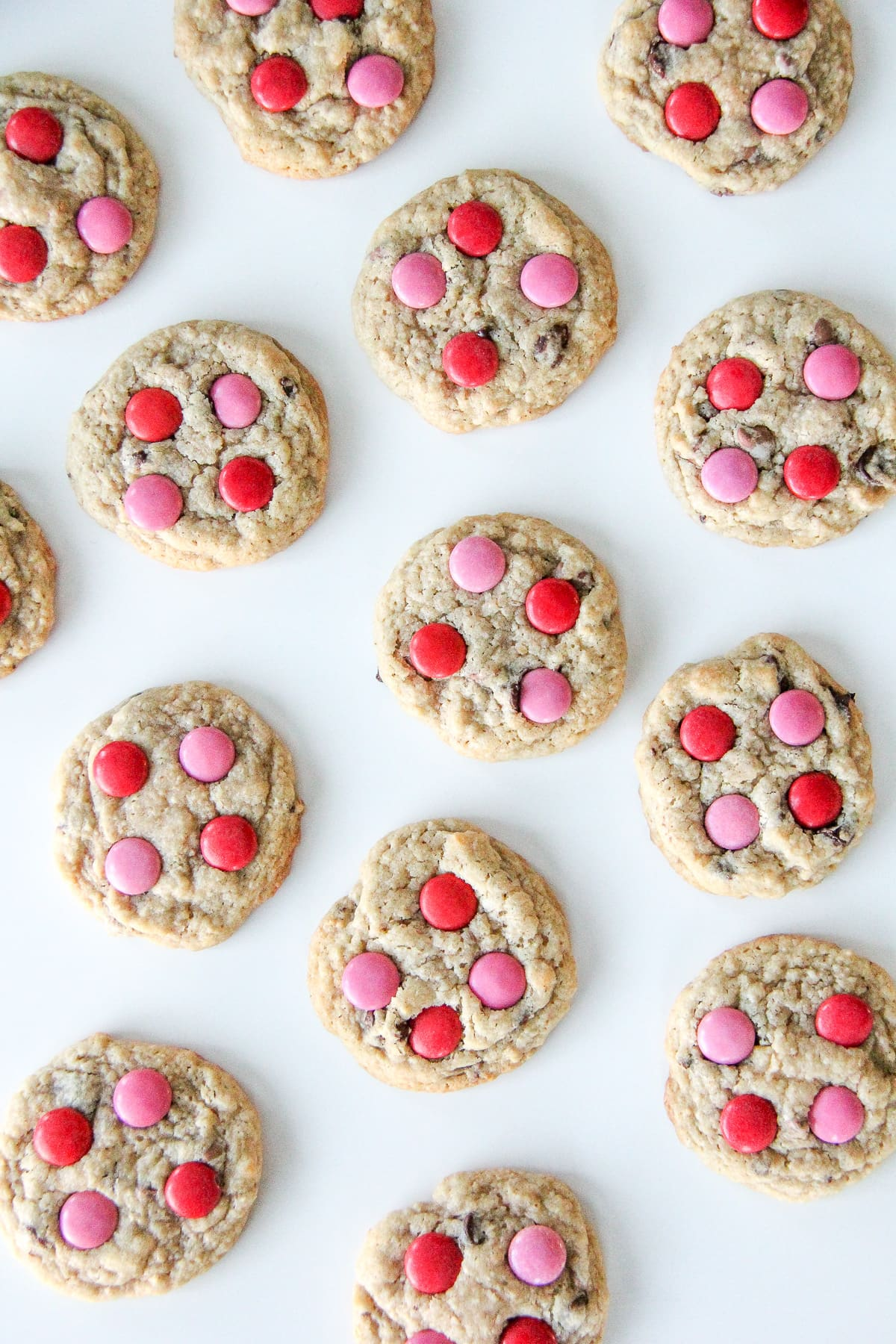 a top down view of chocolate chip cookies with red and pink smarties