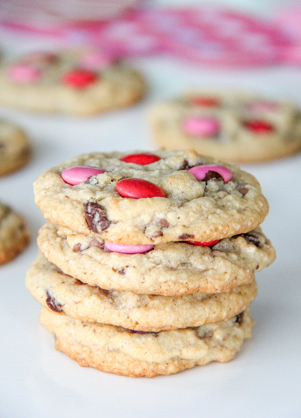 a stack of chocolate chip cookies with red and pink smarties