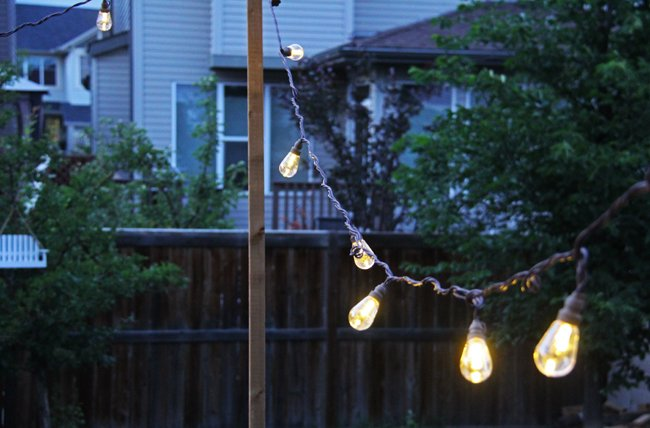 a string of lights outdoors in the evening light