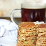 A Zucchini Bread Pancakes next to a cup of coffee