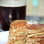A stack of Zucchini Bread Pancakes next to a cup of coffee