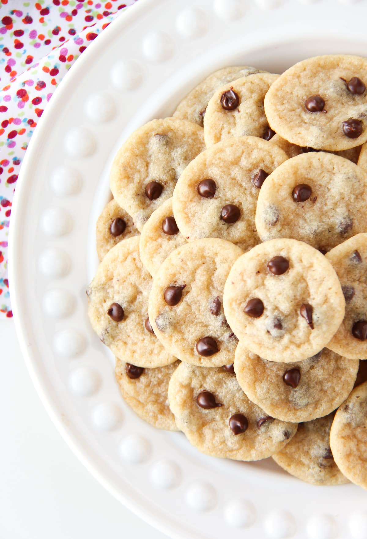 a top down view of a plate of mini chocolate chip cookies. in the background is a polkadot napkin