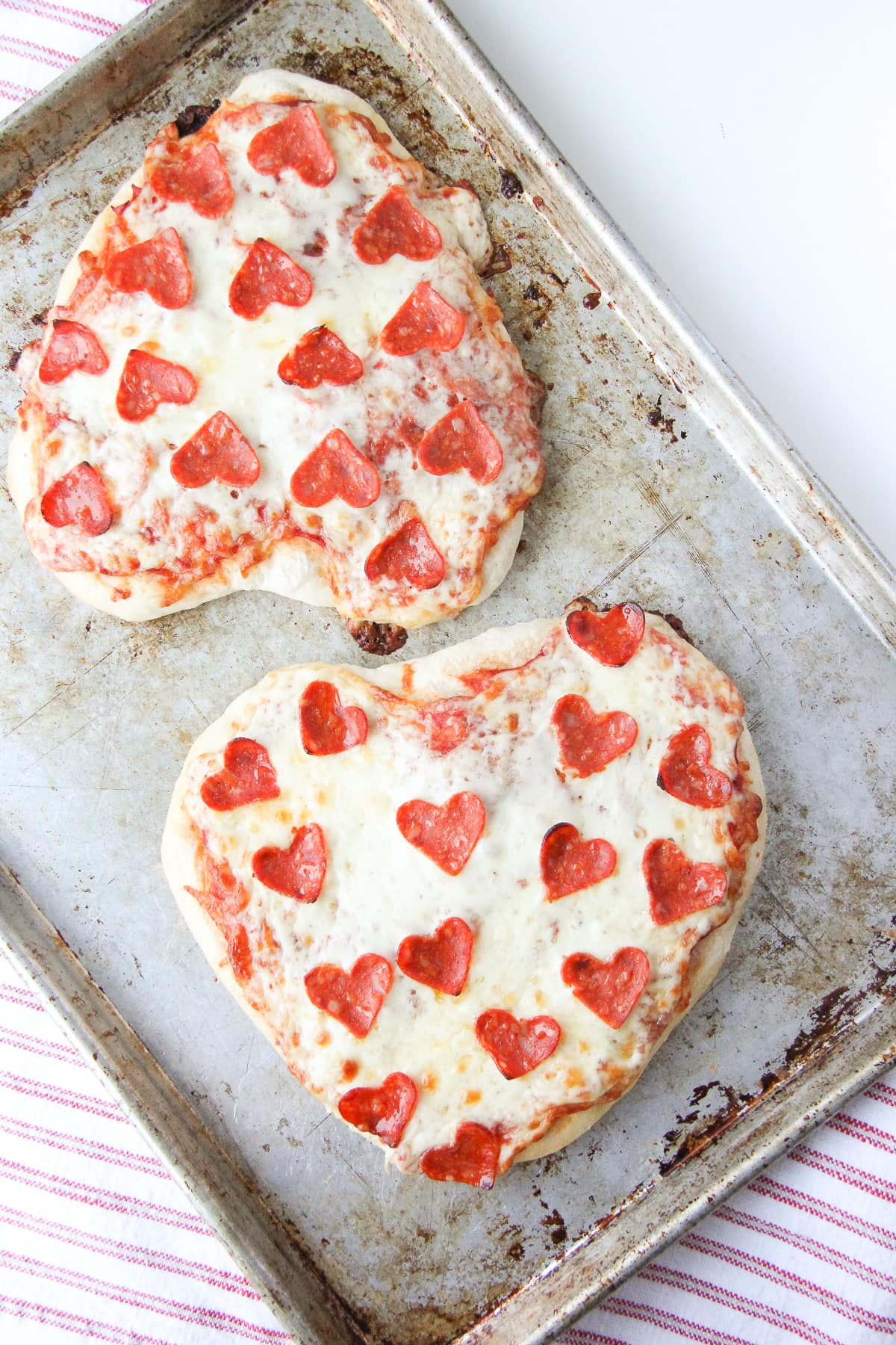 two heart shaped Valentine's Day pizzas with heart shaped pepperoni. they are on a cookie sheet