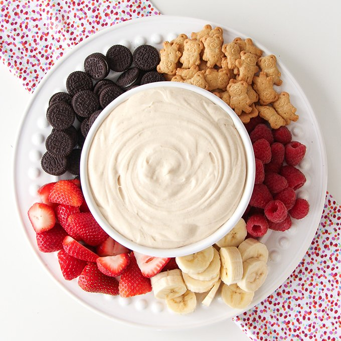 A bowl of Peanut Butter Marshmallow Fluff Dip with strawberries, bananas and cookies for dipping.