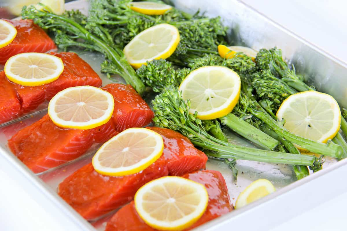 simple summer meals: a sheet pan of slices of raw salmon, lemon and broccolini