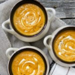 3 bowls of pumpkin soup with swirls of sour cream