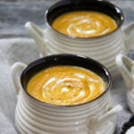 Bowls of pumpkin soup with swirls of sour cream